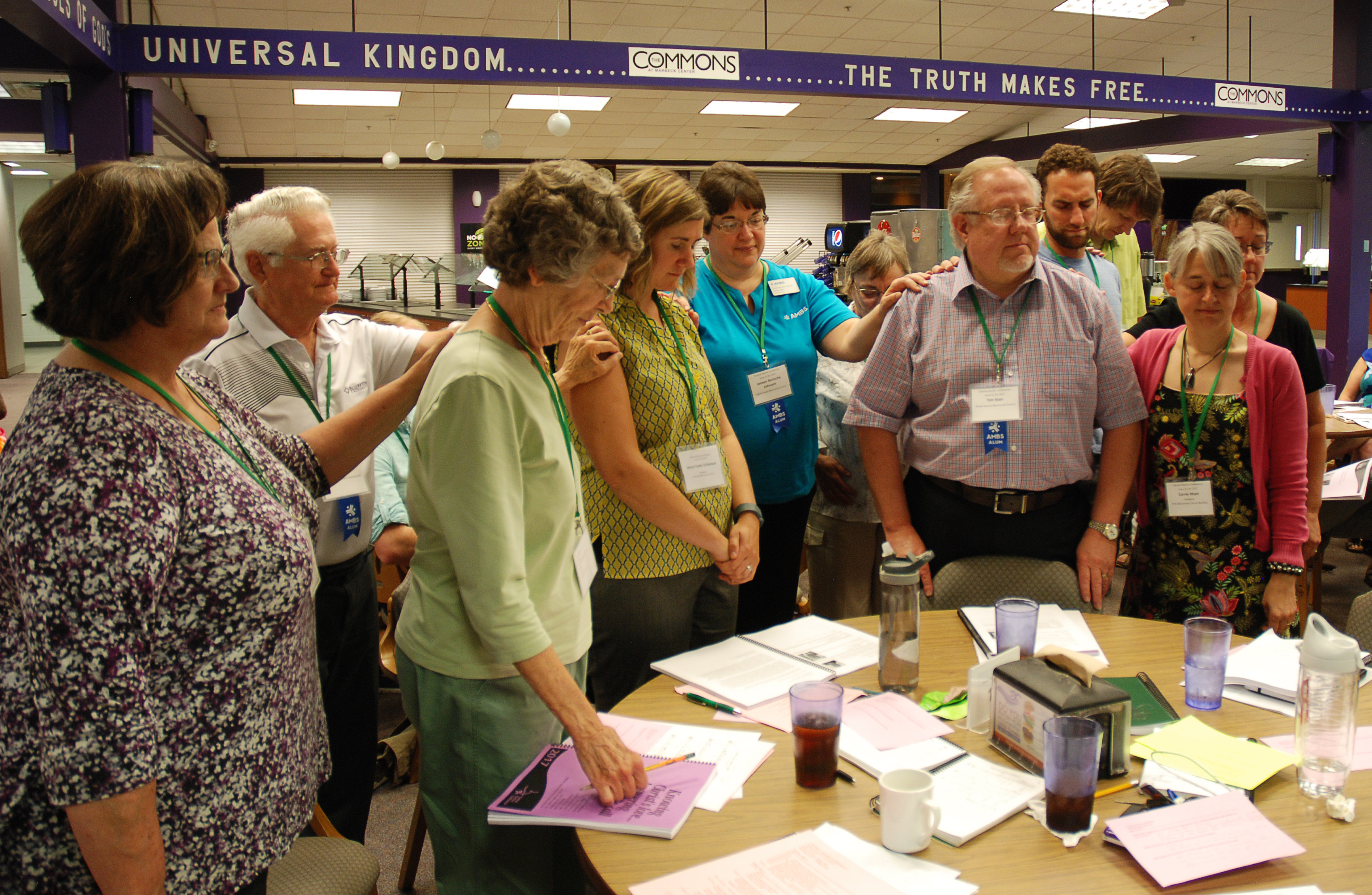 Annual meeting participants at Bluffton University, Bluffton, Ohio, surround new leaders in a commissioning prayer during the Friday morning delegate session, June 23, 2017. This group is blessing Anna Yoder Schlabach, president-elect; and Tim Stair, new member of the Missional Church Committee. (Left to right): Omie Baumgartner, Jim Mohr, Mary Beth Huser, Anna Yoder Schlabach, Janeen Bertsche Johnson, Rosalie Grove, Tim Stair, Jake Hess, Trevor Bechtel, Carrie Mast and Brenda North Martin. Photo by Mary E. Klassen