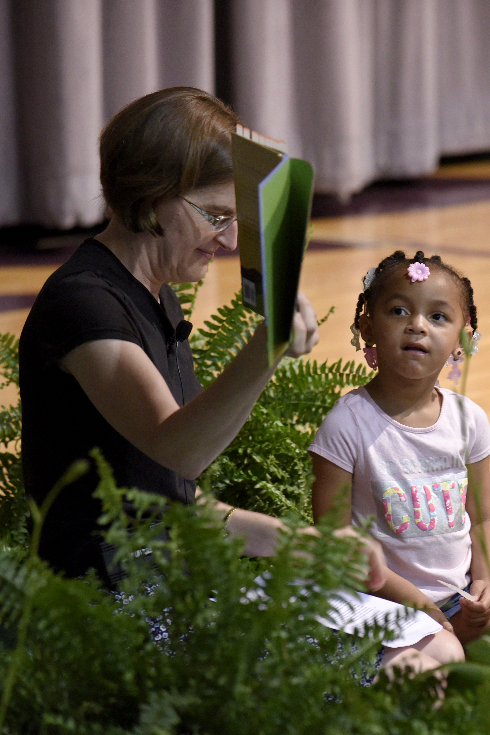 Rylee Tennant (right), age three, listens to Lisa Weaver tell the children's story during the worship service Thursday night during the Central District Conference, Thursday, June 22, 2017, at Bluffton University, Bluffton, OH. Tennant is the grandchild of Stephanie Ingram, who shared her experience with gun violence later in the service. Photograph by J. Tyler Klassen