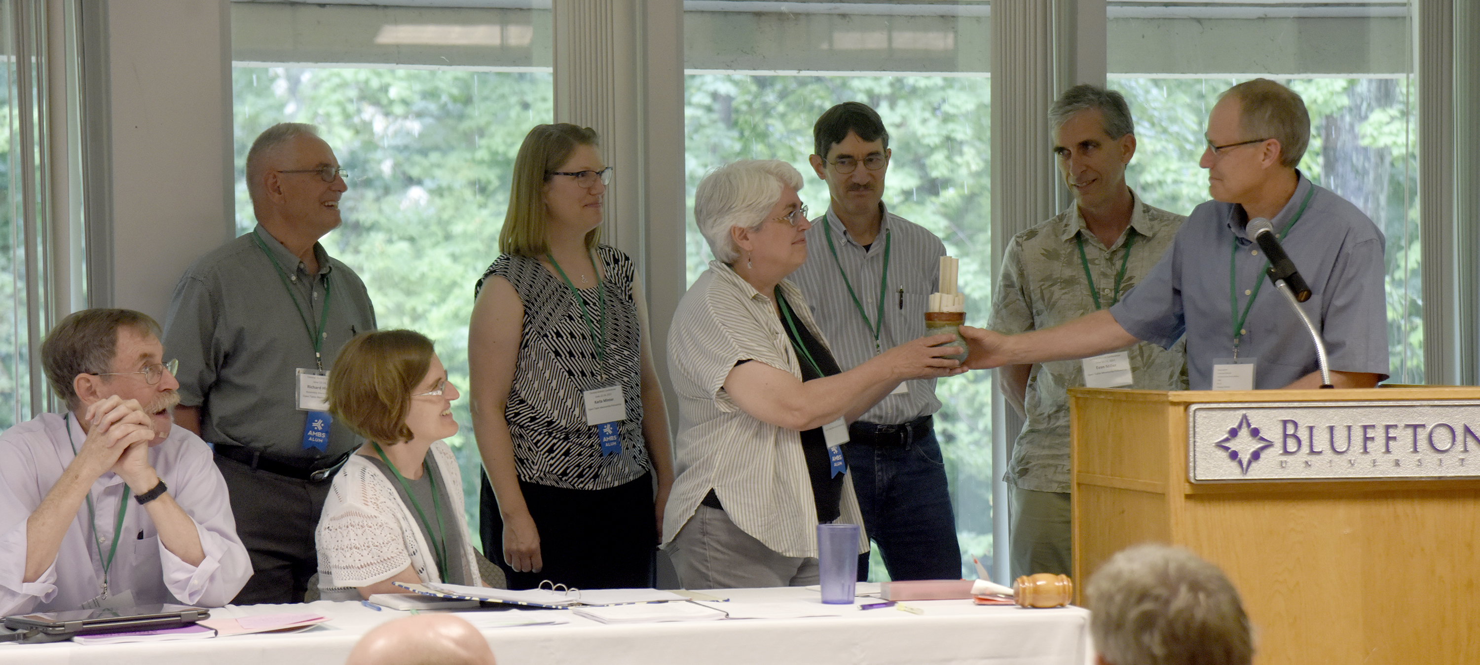 Doug Luginbill (right) hands a cup containing written blessings from Central District churches to Sally Weaver Glick, as Open Table Fellowship, Goshen, IN, was welcomed into Central District during the Central District Conference, Friday, June 23, 2017, at Bluffton University, Bluffton, OH. Seated from left are: Arman Habegger and Lisa Weaver. Standing with Weaver Glick and Luginbill are (from left) Richard Hirschberg, Karla Minter, John Glick, and Evan Miller. Photograph by J. Tyler Klassen