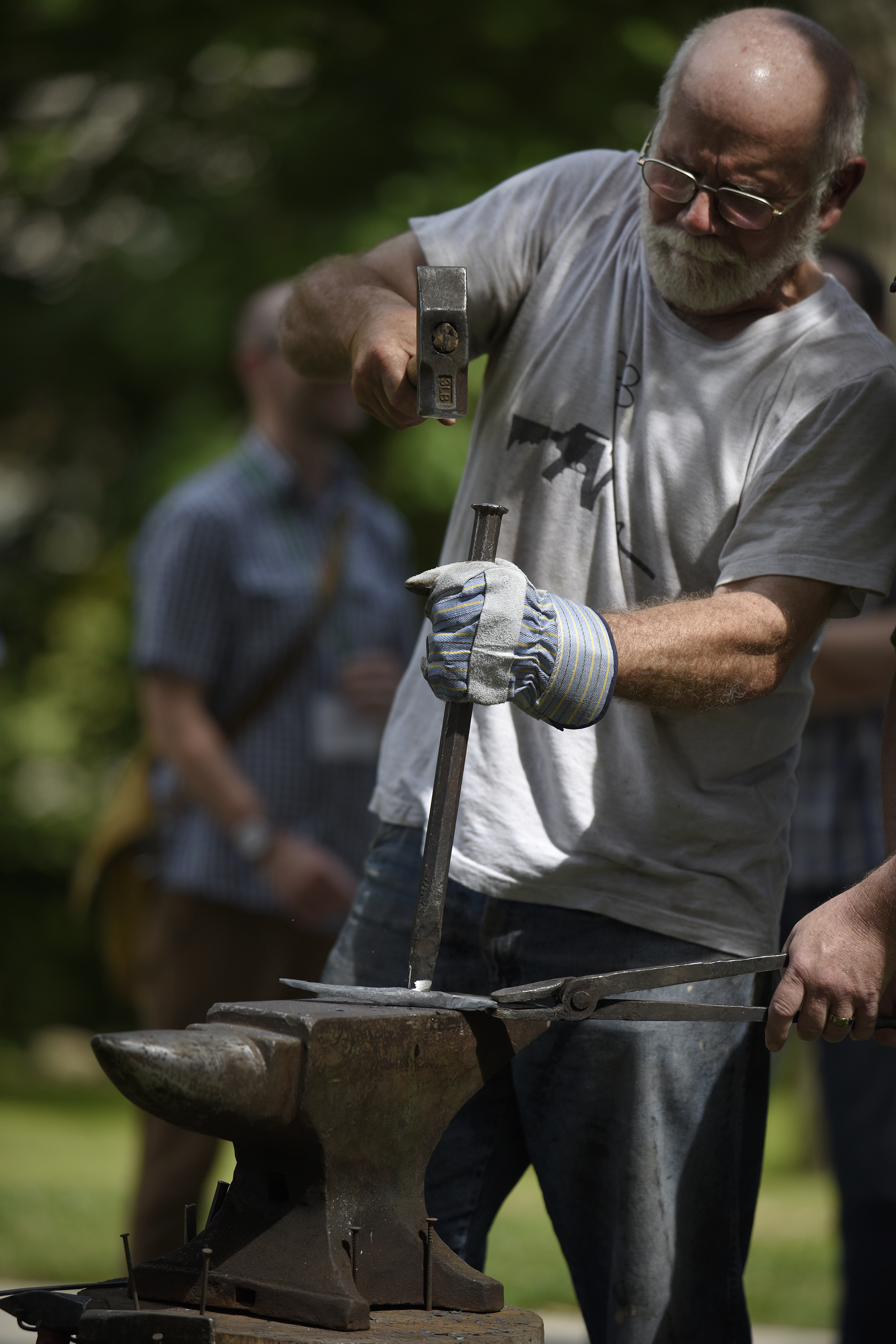 Fred Martin, RAWTools blacksmith, Colorado Springs, CO., works with piece of a gun as he forms a gardening tool during the Thursday session of Central District Conference, Thursday, June 22, 2017, at Bluffton University, in Bluffton, OH. Photograph by J. Tyler Klassen